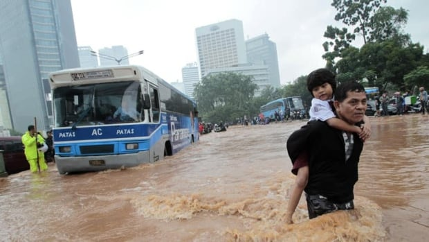 A man carries his son across a flooded area at the business district in Jakarta on Thursday. Water levels reached up to two metres high in some places