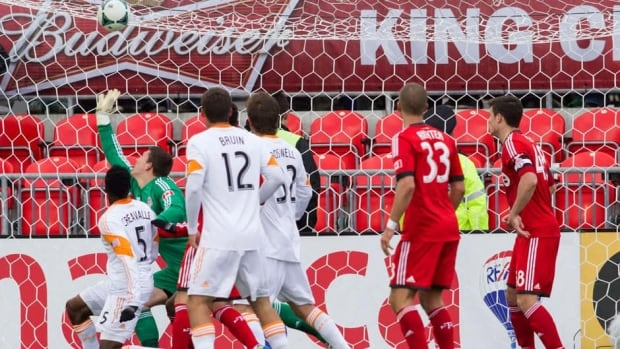 Houston Dynamo's Warren Creavalle, left, heads the ball past Toronto FC 's Joseph Bendik to tie the game in stoppage time in Toronto on Saturday.