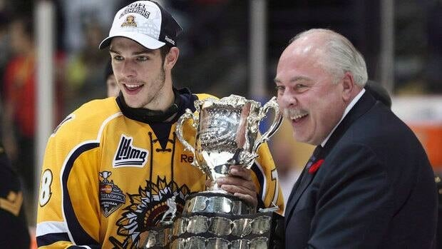 Shawinigan Cataractes captain Michael Bourniva receives the Memorial Cup trophy from CHL president David Branch in this May 27, 2012 photo in Shawinigan Que.