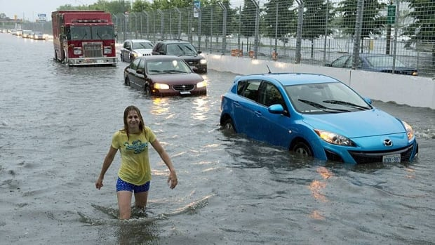 A woman wading through flood water on Lakeshore West during a storm in Toronto on Monday evening. Flash flooding made the city grind to a stop, and many agencies are warning of delays during the day Tuesday.