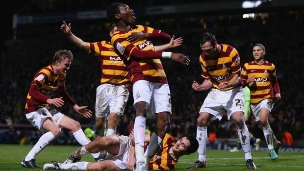 Carl McHugh of Bradford City (grounded) celebrates with teammates after scoring their third goal against Aston Villa at Coral Windows Stadium, Valley Parade on Tuesday Bradford, England.