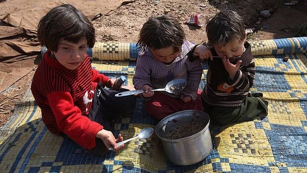 Syrian children eat outside their tent at Atmeh refugee camp in northern Syria in February, 2013. Canadian aid agencies today launched a new appeal for donations to help more than 1.4 million refugees. Hussein Malla/Associated Press.