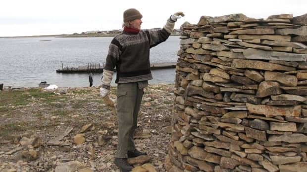 Jan Wanggaard, who is leading the Norwegian effort to bring the Maud back to Norway, piles stones on top of each other for the cairn, a traditional Norwegian-style memorial.