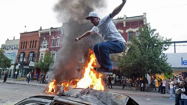 A protester jumps on a burnt-out car as a police car burns in the background during an anti-G20 demonstration June 26, 2010, in Toronto. Police violated civil rights, detained people illegally and used excessive force during the G20 summit two years ago, a new report concludes.