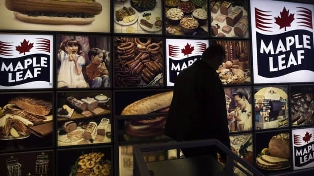 A Maple Leaf Foods employee walks past a Maple Leaf sign at the company's meat facility in Toronto. The company has sold its Rothsay unit to Darling International of Texas.