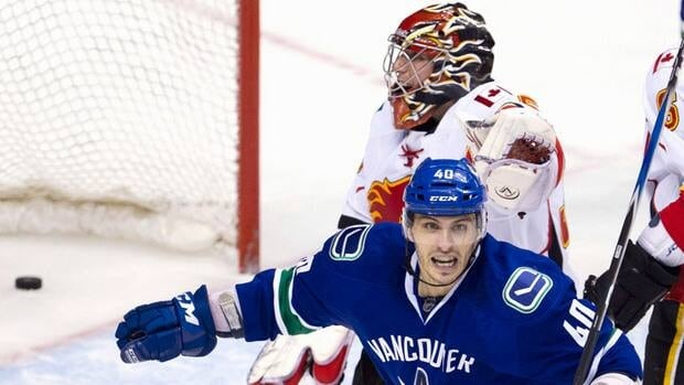 Calgary Flames goalie Henrik Karlsson (35) looks on as Vancouver Canucks centre Maxim Lapierre (40) celebrates teammate Vancouver Canucks defenseman Marc-Andre Gragnani's, not shown, goal during the third periodin Vancouver on Saturday.