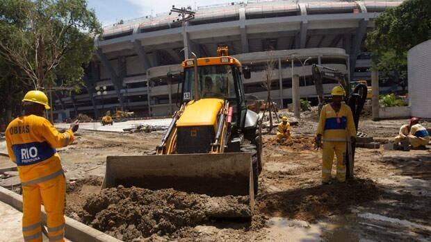 Workers remove mud after heavy rains outside Maracana stadium in Rio de Janeiro,  on March 6.