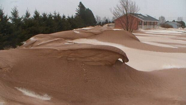 Snow drifts look more like sand dunes with their covering of soil blown off nearby fields.