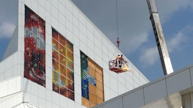 Workers reinstall the stained-glass solar windows that broke last year on the Cathedral of the Holy Family in Saskatoon.