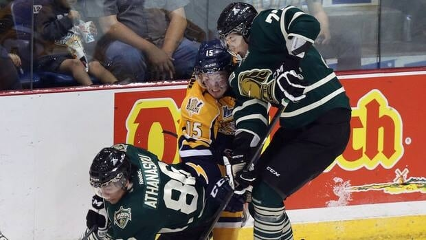 Shawinigan Cataractes' Jonathan Narbonne, centre, is squeezed between London Knights players Andreas Athanasiou, left, and Josh Anderson during first period.