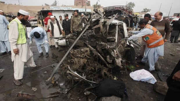 Rescue workers collect body parts after a bomb attack at Fauji Market in Peshawar on Monday.