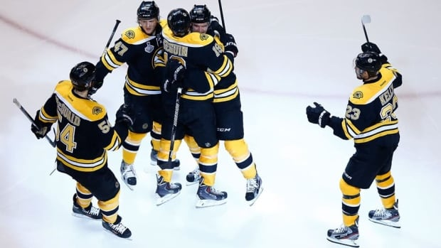 Daniel Paille (20) of the Boston Bruins is congratulated by teammates Torey Krug (47), Tyler Seguin (19),  Adam McQuaid (54), and Chris Kelly (23)after scoring a goal in Game 3 of the Stanley Cup final on Monday.
