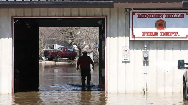 Firetrucks were moved to safety as the rising waters from the nearby Gull River flood the downtown section of Minden, Ont., on Monday.