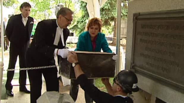 Steve Lalanchette passes the Alberta legislature time capsule to Speaker Gene Zwozdesky and Culture Minister Heather Klimchuk on Monday.