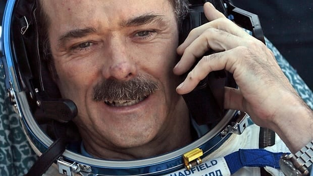 Chris Hadfield speaks on a cellphone shortly after the Soyuz space capsule carrying him and two other astronauts from the International Space Station landed on the steppes of Kazakhstan on May 14, 2013.