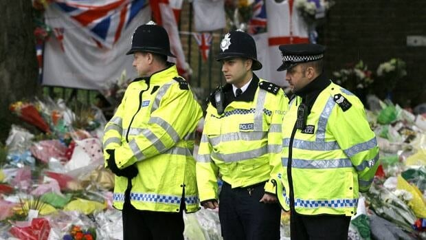 Police officers stand guard near some of the thousands of floral and other tributes left in honour of soldier Lee Rigby, slain near Woolwich Barracks in London. The gruesome scene of the killing was captured by witnesses' cellphones.