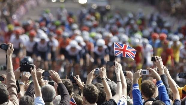 Spectators cheer and takes pictures as the pack ride past during the men's road cycling race at the 2012 Summer Olympics on July 28 in London. The IOC said enthusiastic fans tweeting and texting their impressions of the race from the sidelines overloaded GPS and data networks and interfered with the Olympic coverage of television broadcasters such as the BBC.
