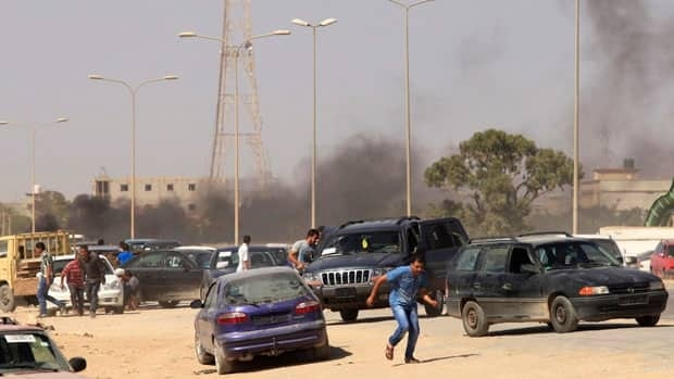 Protesters run after an attack on the headquarters of a Libyan militia, the Libya Shield brigade, in Benghazi.