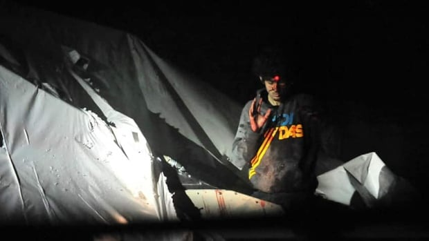 One of the photos released to Boston Magazine by Massachusetts State Police photographer Sgt. Sean Murphy showing Dzhokhar Tsarnaev with the red dot of a sniper's rifle laser sight on his forehead as he is captured on April 19, 2013.