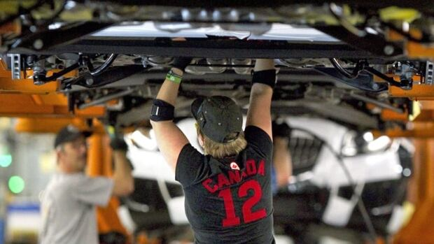 Assembly line workers at the General Motors Assembly plant in Oshawa work on cars in December 2011. The Canadian Auto Workers union has said that three tentative deals reached with the so-called Big Three U.S. automakers will improve competitiveness.