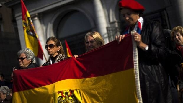 Far right wing supporters hold a pre-constitutional flag outside the Opera House during an act against the independence of Catalonia and to remember former Spanish Dictator Gen. Francisco Franco on the 37th anniversary of his death, in Madrid, Sunday.