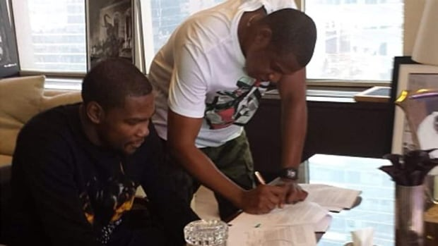 Rap mogul Jay-Z, right, is shown in this photo signing NBA star Kevin Durant to a contract with his sports agency Roc Nation.