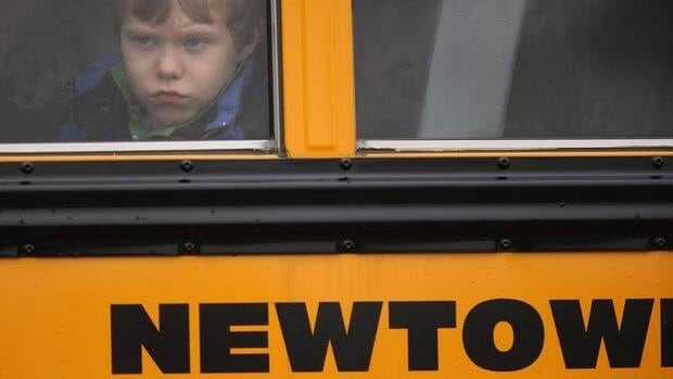 A child gazes from a school bus as it passes by St. Rose of Lima Catholic church in Newtown, where mourners gathered for a funeral service for one of the young shooting victims on Dec. 18, 2012.