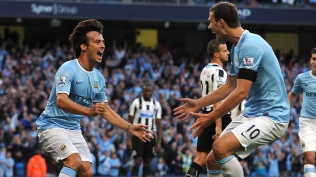 Manchester City's David Silva, left, celebrates with teammate Edin Dzeko after scoring against Newcastle United at The Etihad stadium in Manchester on August 19, 2013.