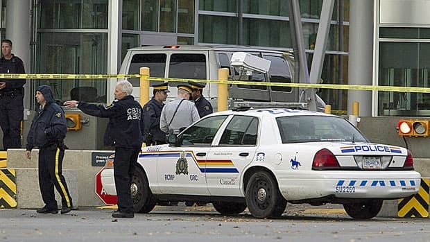 Police investigate a shooting at the border crossing in Surrey, B.C., last October in which a Canadian border guard was shot by a man who then killed himself. A cross-border pilot project that would see joint patrols between Canadian and U.S. police officers is being delayed by U.S. demands its officers be exempt from Canadian law.