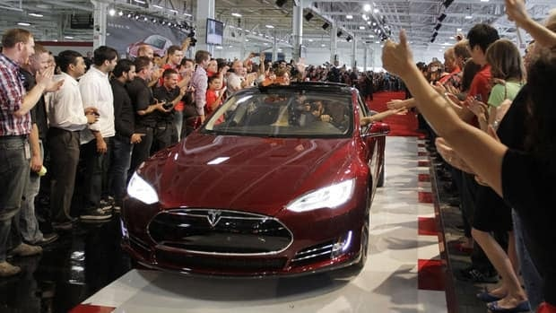 In this June 22, 2012 file photo, Tesla workers cheer the first Tesla Model S cars sold during a rally at the Tesla factory in Fremont, Calif. The Tesla Motors Inc. Model S electric car has tied an older Lexus for the highest score ever recorded in Consumer Reports magazine's automotive testing.