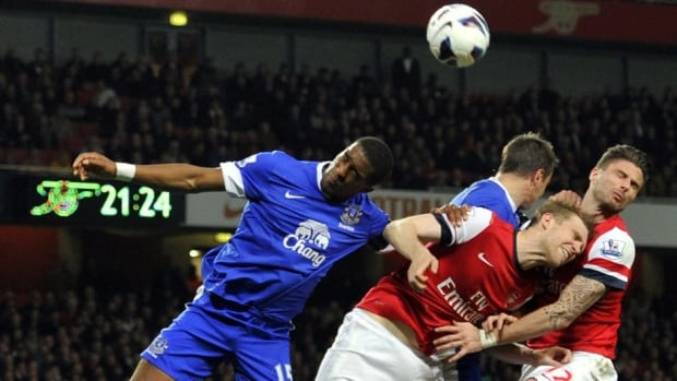 Everton's French defender Sylvain Distin, left, heads the ball clear against Arsenal at The Emirates Stadium in north London on Tuesday.