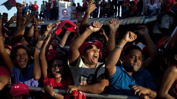 Supporters cheer for Venezuela's President Hugo Chavez during a campaign rally in Guarenas, Venezuela, on Sept. 29, 2012. Venezuelan officials say two people were killed after clashes betweeen Chavez loyalists and supporters of his opponent in the upcoming presidential election.