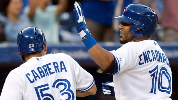 Edwin Encarncacion, right, is congratualted by Blue Jays teammate Melky Cabrera after scoring on Encarnacion's homer against the Rockies in the fifth inning Tuesday night. Encarnacion has 19 homers and 41 RBIs in 54 interleague matchups while Cabrera is Toronto's top hitter for average in interleague play this season among the regulars at .327.