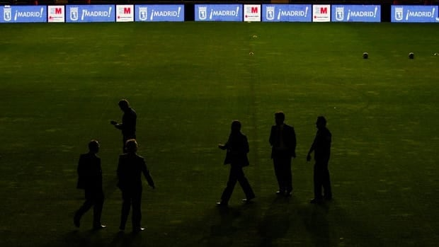 Real Madrid's team officials walk on the pitch as the Spanish La Liga soccer match against Rayo Vallecano is canceled due to an electrical problem at the Teresa Rivero stadium in Madrid, Spain, Sunday.