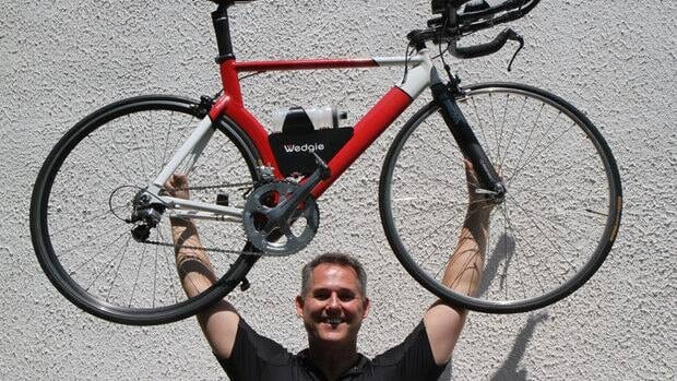 Tom Schopf's clients, who use the Wedgie, hold their bikes over their heads for photo ops all the time. We decided he should, too.