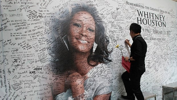A Filipino fan writes a message on a Manila tribute wall for American singer Whitney Houston, who died in February. Fans around the world mourned the death of the influential singer.