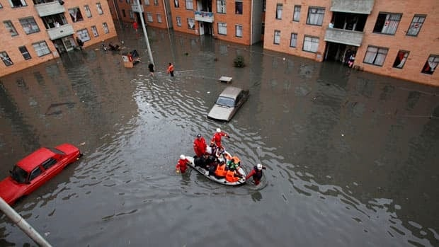 Firefighters evacuate residents from a flooded neighbourhood in Patio Bonito, Colombia last December. The recent study presents some of the growing evidence that global warming is responsible for an increase in heavy rain events that lead to flooding.