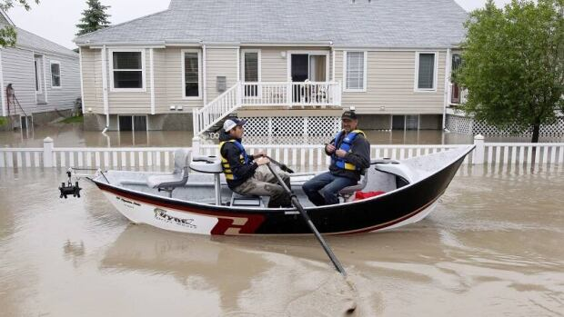 Two men use a fishing boat to rescue residents from a neighborhood after heavy rains caused flooding, closed roads, and forced evacuation in High River, Alta., on Thursday.