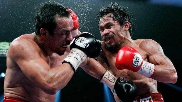 Manny Pacquiao, right, of the Philippines, hits Mexico's Juan Manuel Marquez during a WBO welterweight title fight Saturday night. Pacquiao narrowly escaped with the title, winning by decision.