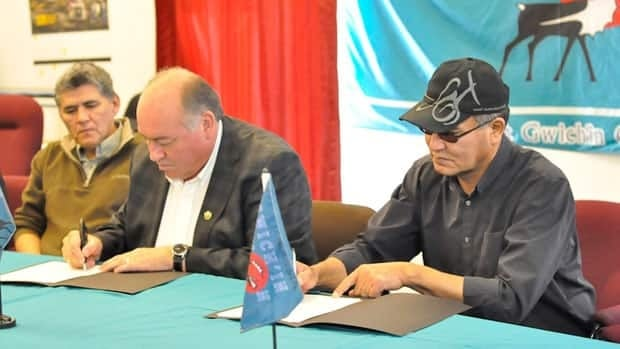 Minister Robert C. McLeod, who is also the MLA for Inuvik Twin Lakes, looks on as N.W.T. Premier Bob McLeod and Gwich'in Tribal Council president Robert Alexie Jr. sign the devolution Agreement in Principle in Aklavik, N.W.T., last week.