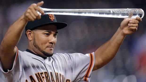 This July 10, 2012 file photo shows National League's Melky Cabrera, of the San Francisco Giants, showing off his MVP trophy after the MLB All-Star baseball game in Kansas City, Mo. Cabrera has been suspended for 50 games without pay after testing positive for testosterone.