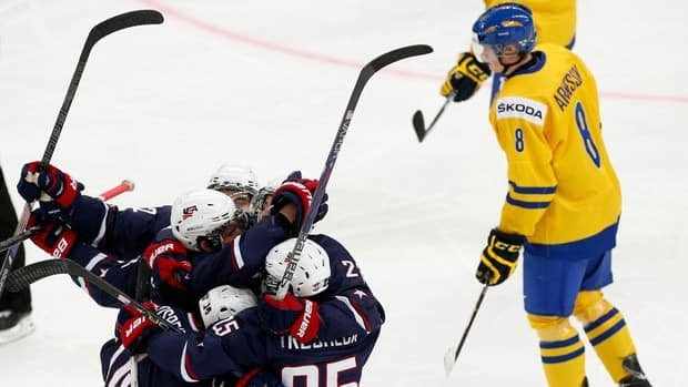 American players celebrate their second goal as Sweden's Linus Arnesson skates by during the second period of their gold medal game in Ufa, Russia on Saturday.