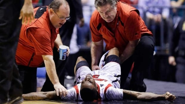 Trainers check on Louisville guard Kevin Ware after he injured his lower right leg during the first half of the Midwest Regional final against Duke on Sunday in Indianapolis. Ware left the court on a stretcher.