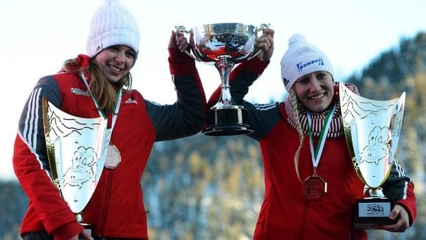 Canada's Kaillie Humphries and Chelsea Valois hoist the trophy after winning the women's bobsleigh title on Saturday.
