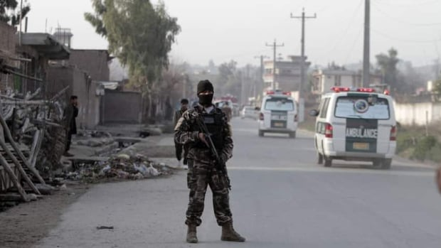 A security official stands guard at the scene of a suicide car bomb attack which killed and injured several people at the National Directorate of Security in Jalalabad, Afghanistan.