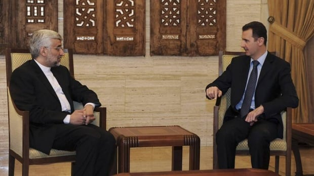 Syria's President Bashar Assad (right) meets Iran's Supreme National Security Council Secretary Saeed Jalili in Damascus on Sunday. Jalili says Iran supports any initiative for dialogue to end the fighting in Syria, but stipulates the talks must be in Damascus.