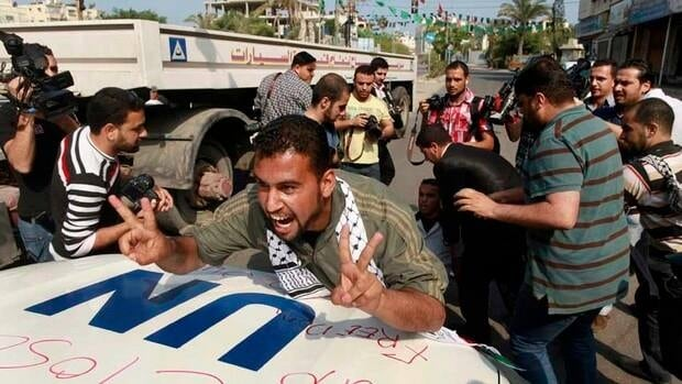 A Palestinian protester gestures in front of a UN vehicle during a protest in Gaza City to show solidarity with Palestinian prisoners held in Israeli jails.