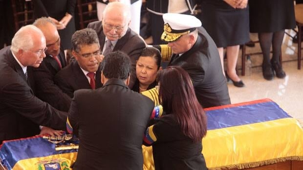 Venezuelan government officials join hands over the flag-draped casket of Venezuela's late President Hugo Chavez during a funeral ceremony at the military academy in Caracas.