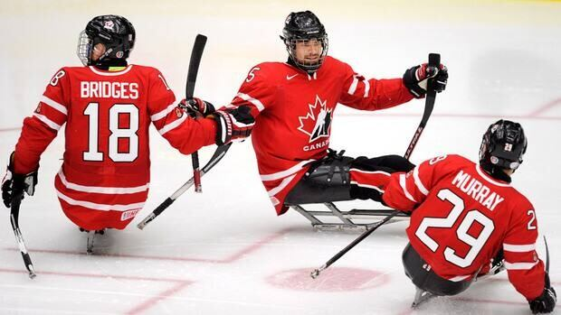 Canada's Kevin Rempel, centre, celebrates his second-period goal against Japan with Billy Bridges, left, and Graeme Murray during semifinal World Sledge Hockey Challenge action in Calgary, Alberta on Thursday.