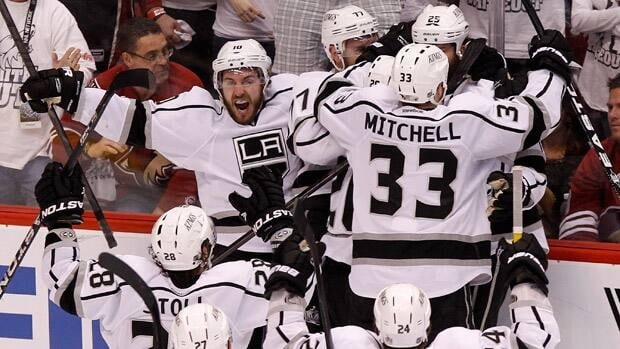 Los Angeles Kings' Mike Richards (10) shouts in celebration as teammates converge on Dustin Penner (25), who scored the game-winner against the Phoenix Coyotes in overtime during Game 5 on Tuesday in Glendale, Ariz.